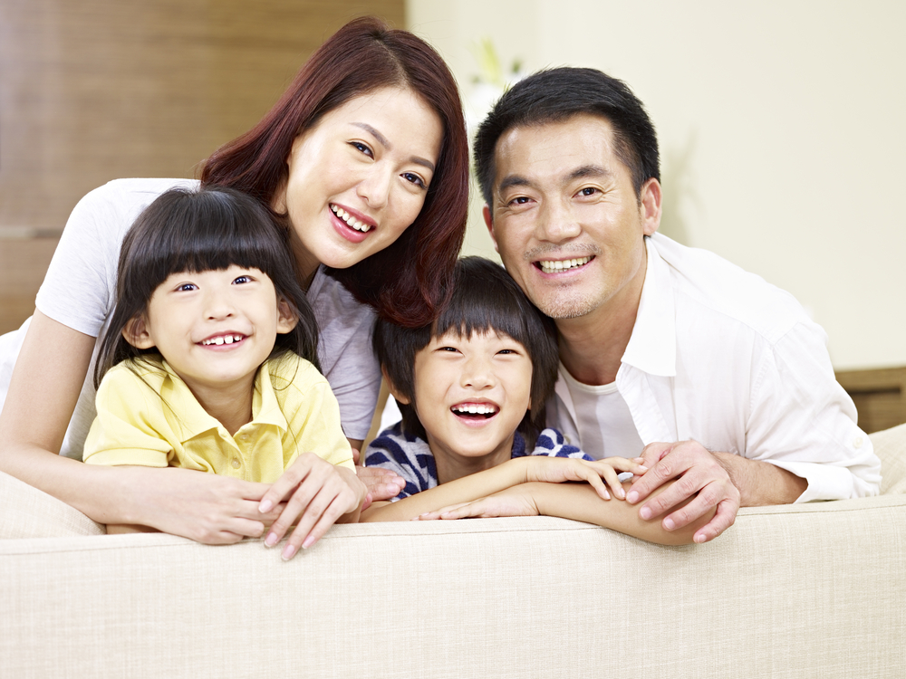 Portrait of an Asian family with two children, happy and smiling.