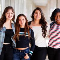 Portrait Of Smiling Female High School Student Friends In Corridor Of Building.