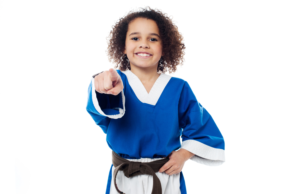 Cheerful karate kid pointing you out.
