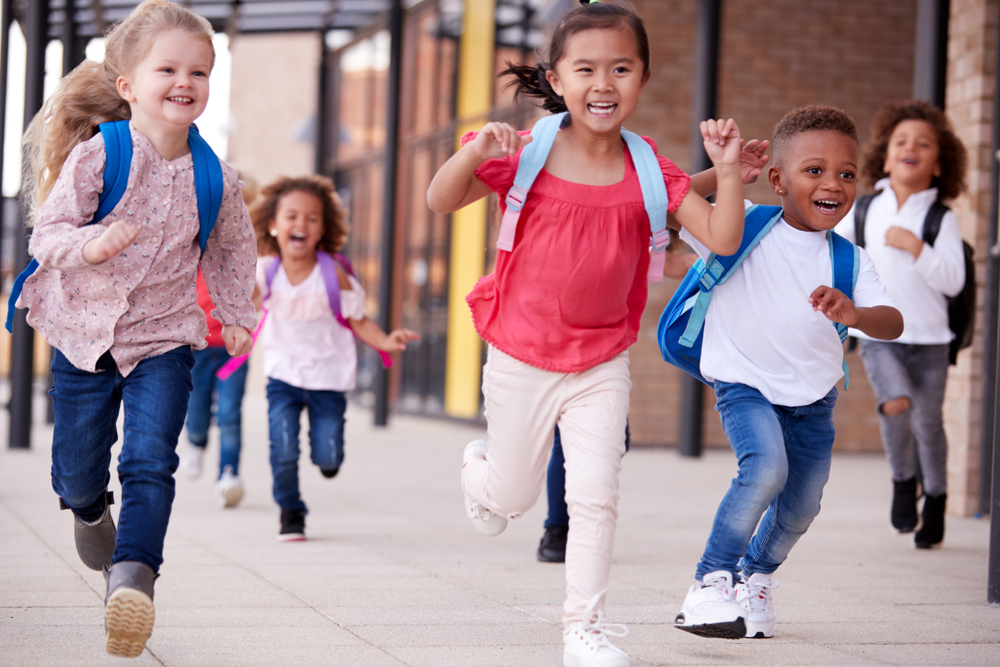 A group of smiling multi-ethnic school kids running in a walkway outside their infant school building after a lesson, close up
