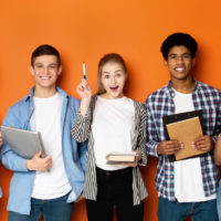 Education concept. Teen friends with copybooks and earth globe, orange background.