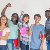 Smiling and enjoying multi ethnic teenagers schoolmates, isolated on white background