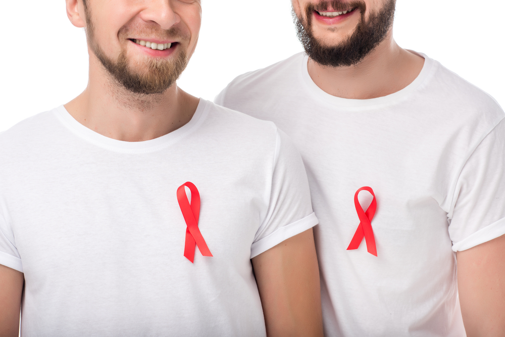 cropped shot of smiling gay couple with aids ribbons isolated on white