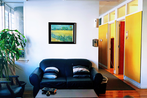 Sunny and brightly colored room with a sofa. There's a hallway on the right side with open doorways.